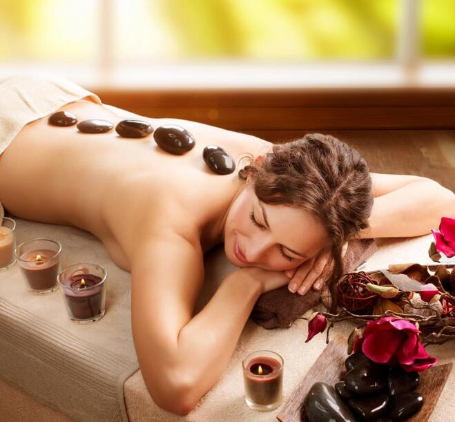 A woman lying in a spa with stones at her back